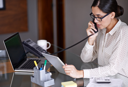 Woman seated at a desk, answering the phone at one of our referrals